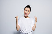 Happy young woman with winner gesture
