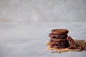 Stack of fresh homemade crispy cookies with dark chocolate.On a gray background. Copy space