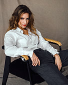 Fashion beauty portrait model in classic suit, white shirt posing on chair