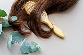 female hair,  bamboo comb, eucalyptus leaves on beige background top view, flat lay. copy space. Self care, hair treatment  concept.