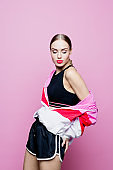 Fashion portrait of sensual woman in sports clothing against pink background