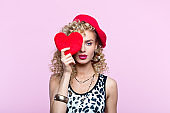 Pretty woman in 80's style outfit holding plush heart