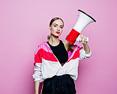 Sports portrait of beautiful woman in 80's style tracksuit holding megaphone