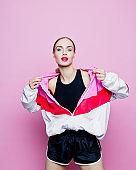 Fashion portrait of beautiful woman in tracksuit against pink background