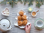 Creative Xmas table setup for tea. Top view with eclairs, brewing cakes. Hand holds plate with cakes in shape of Christmas tree. Fir twigs with light garland on stripy textile tablecloth