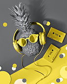 Illuminating Yellow and Ultimate Gray, colors of the year 2021. Pineapple in earphones