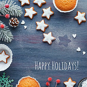 Christmas background with star cookies, tasty lemon muffins, winter decor. Text Happy Holidays