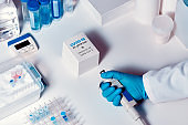 Quick novel COVID-19 coronavirus test kit. 2019 nCoV pcr diagnostics kit. Hand in glove holds pipette. Kit detects covid19 virus in patients samples. Тesting system for real-time PCR amplification.