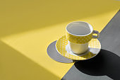 Illuminating Yellow and Ultimate Gray, colors of the year 2021. Yellow ceramic cup on geometric layered yellow grey background. Sunlight, long shadows, isometric projection