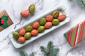 Walnut shaped Cookies with Dulce De Leche. Tasty creative dessert in green and red on marble table with winter decorations
