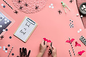 Trick or treat text on pink paper background. Flat lay, hands with scissors and Halloween decor. Hexagon confetti, drink straws, bats, sugar hearts and spiders.