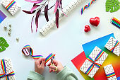Wrapped gift boxes with LGBT rainbow ribbon. Flat lay with Christmas or Valentine's day decor