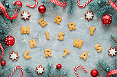 Dyslexia awareness, disorganized cookie letters spelling Merry Christmas. Fir twigs and Xmas decor