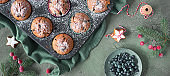 Blueberry muffins with sugar icing in a baking tray. Panoramic top view image with Xmas decor