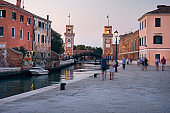 Venice, Italy - September 18, 2020: People walk along canal by Arsenal water gate. Venice, Italy during the coronavirus pandemic