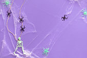 Minimal Halloween background with hung skeleton, spider web and line of black spiders on vibrant purple neon paper. Top view, trendy background.