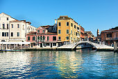 Traditional houses and pedestrian bridge in Venice, Italy on a sunny day