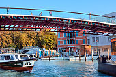 Boat going underneath pedestrian bridge across Grand Canal in Venice, Italy