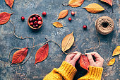 Fall decorations made from natural materials. Making garland with hemp cord and vibrant red Autumn leaves.