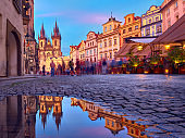 St Mary Tyn Church in Prague with reflection in a pool of water after Summer rain with tourists walking by towards Old Town Square. Romantic Prague, travel background at sunset.