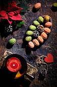 Walnut shaped cookies with Dulce De Leche or sweetened condensed milk. Tasty creative dessert on dark background with natural decorations. Fir twigs, poinsettia, red candle on old book, heart