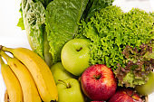 Bio-organic salad vegetables, apples, bananas in a basket. Good for health. Diet in the white background.