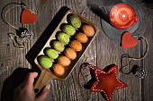 Walnut shaped cookies with Dulce De Leche or sweetened condensed milk. Tasty creative dessert on dark wooden table with natural decorations. Fir twigs, frosted cones soft star, hearts