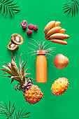 Assortment of tropical fruits and orange smoothie bottle on vibrant bold green background. Pineapple, kiwano, kiwi , lichee and banana - exotic fruits, levitation and vitamin balance.