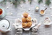 Creative Xmas table setup for tea. Top view with eclairs, brewing cakes. Hands in gloves show plate with cakes in shape of Christmas tree. Fir twigs with light garland on stripy textile background