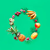 Assortment of tropical fruits flying in circle on green background. Pineapple, kiwano, kiwi , lichee, banana - levitation of exotic fruits. Square composition, copy-space.