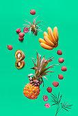 Assortment of tropical fruits and orange smoothie bottle on green background. Pineapple, kiwano, kiwi , lichee and banana. Assortment of exotic fruits, levitation and balance.
