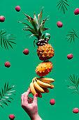 Assortment of tropical fruits, pyramid balancing o human hand on green background. Pineapple, kiwano, kiwi , lichee and banana - tower made of exotic fruits.