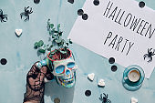 Halloween background on mint blue stone with hand holding skull cup with eucalyptus. Top view with paper confetti, sugar hearts, drink straws and spiders.