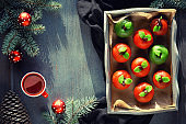 Marzipan sponge apples. Christmas dessert with cup of tea, fir twigs, green candle, pine cone, Xmas toys. Top view on in rustic wooden tray on textile cotton towel