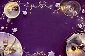 Christmas table setup with white and gold. Flat lay, copy-space on dark purple linen tablecloth.