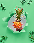 Small ripe orange pineapple cradled in human hand. Hand with the fruit in torn paper hole. Tropical neo mint green geometric background with palm leaves