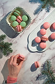 Pink and mint green macaroons on a tray and in ceramic bowl. Female hand holding tasty snack. Creative wintertime sweets in green and red on marble table with fir twigs