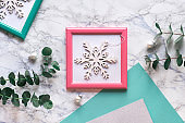 Geometric Christmas flat lay with pink and green frames and green paper. Fresh fragrant eucalyptus twigs and decorative flat white snowflake in pink frame. Flat lay on light marble background.