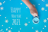 Text Happy New Year 2021. Child's hand holding blue alarm clock showing five to twelve with paper snowflakes.