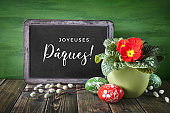 """Words """"Happy Pques"""" mean """"Happy Easter"""" in French language. Primrose flower pot, red and green wooden Easter eggs and blackboard with greeting on rustic wood."""