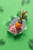 Small ripe orange pineapple in human hand, the other hand showing OK sign. Hands with the fruit show out of ripped paper hole. Tropical green geometric background with natural palm leaves