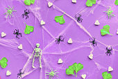 Creative Halloween background with neon green ginkgo leaves, spider web and black spiders on neon purple paper. Flat lay, top view, trendy background.