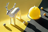 Illuminating Yellow and Ultimate Gray, colors of the year 2021. Ceramic deer, burning candle, cotton flower and balls on split yellow grey background. Sunlight, long shadows