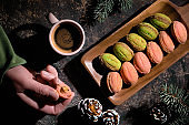 Walnut shaped cookies with Dulce De Leche or sweetened condensed milk. Creative flat lay on dark table decorated with fir twigs, cones, red ribbons, cup of coffee. Hand with half cookie