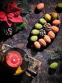 Walnut shaped cookies with Dulce De Leche or sweetened condensed milk. Tasty creative dessert on dark background with natural decorations. Fir twigs, poinsettia, red candle on old book