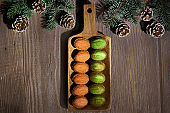Walnut shaped cookies with Dulce De Leche or sweetened condensed milk. Tasty creative dessert on dark background with natural vintage decorations. Fir twigs, frosted cones on dark table, copy-space