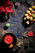 Cookies in walnut shape filled with Dulce De Leche or sweetened condensed milk. Creative dessert on dark table with natural vintage decorations. Fir twigs, poinsettia, red candle on old book, cones