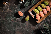 Walnut shaped cookies with Dulce De Leche or sweetened condensed milk. Tasty creative dessert on dark background with natural vintage decorations. Fir twigs, frosted cones on dark table, text space