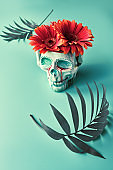 skull with coral color gerbera flowers and palm leaves on mint green background. Creative concept. Surreal feel, eery spooky atmosphere.