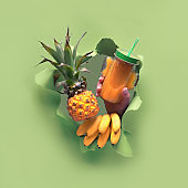 Small ripe orange pineapple in human hand, the other hand showing OK sign. Hands with the fruit show out of torn paper hole. Tropical green geometric background with palm leaves